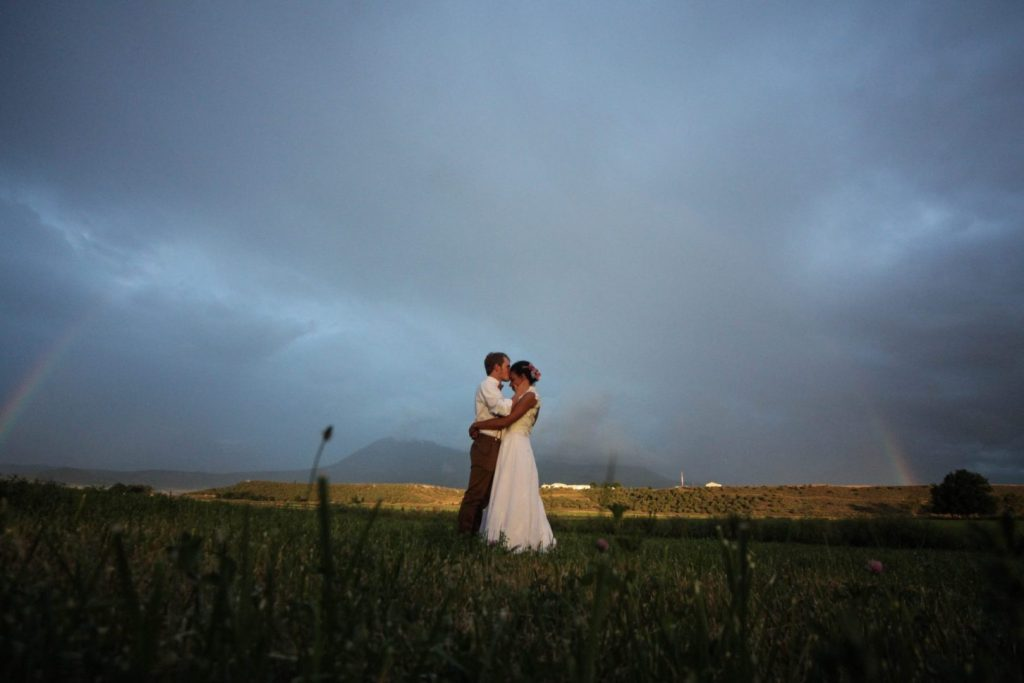 bride and groom with colorado mountain rainbow