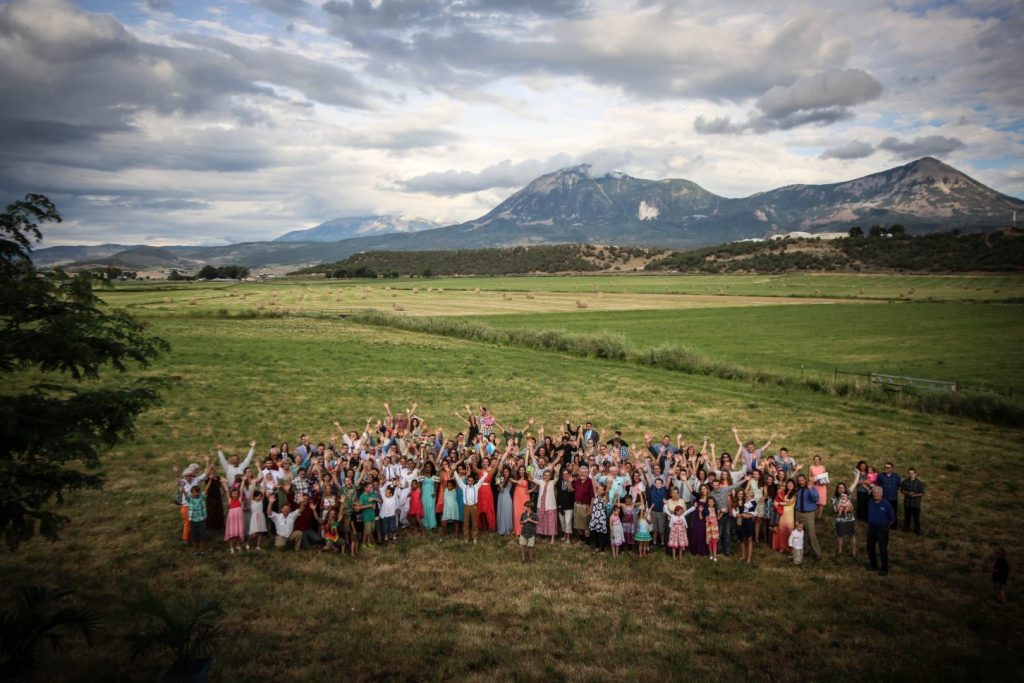 Large group wedding photo with mountains