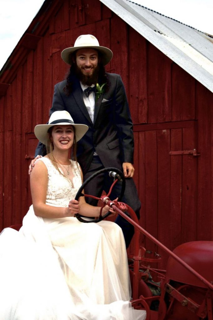 Bride and groomon all Farmall Tractor in front of red shed
