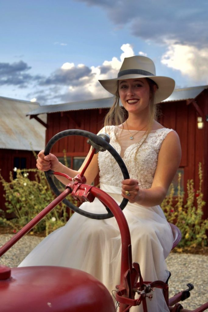 Bride on red tractor with red out building in background