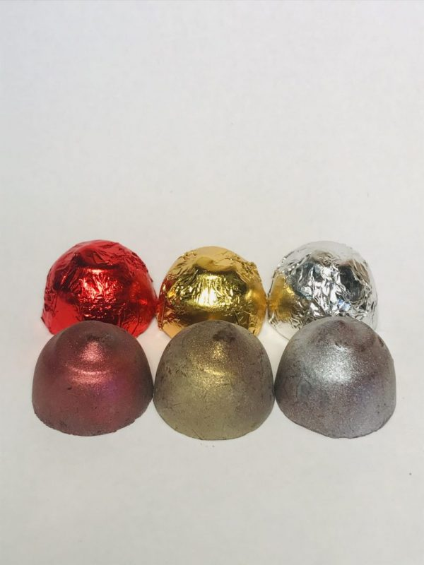 Three CBD chocolates wrapped in red, gold and silver foil and three unwrapped Glazed CBD Chico led with a sparkling finish.