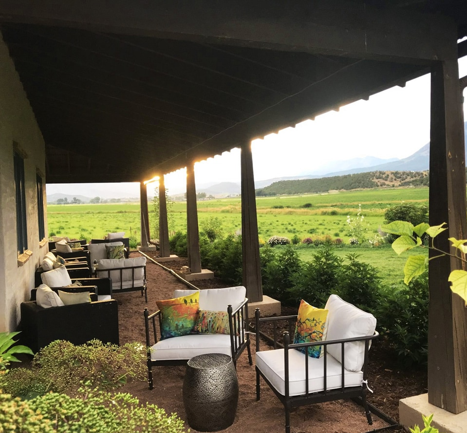 Farm house patio & lounge for enjoying CBD products with rocky mountain background